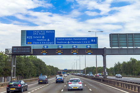 highway sign: Intensive left-hand traffic on British four lane motorway M4 between Windsor and London  with active electronic overhead information sign at grey cloudy  summer day. UK