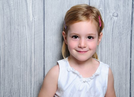 engaging: Portrait of a cute four-year smiling blonde girl in white dress and colorful barrettes in her hair standing on paper gray  wooden fence background