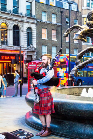 scot: Unidentified young man with a bagpipe in the Scottish national dress at Piccadilly Circus. London. UK