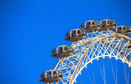 millennium wheel: LONDON, UK - JUNE 5, 2015: Moving London Eye on blue sky background. London Eye is a giant Ferris wheel situated on the banks of the River Thames