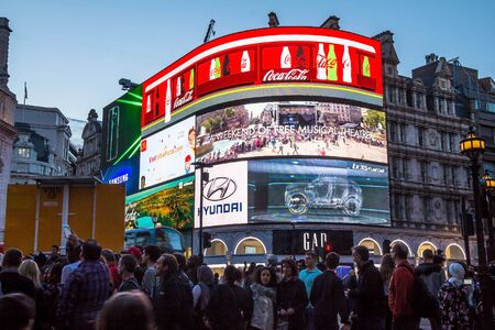 piccadilly: Tourists visit famous Piccadilly Circus  with neon signage that has become one of major attraction of London. UK Editorial