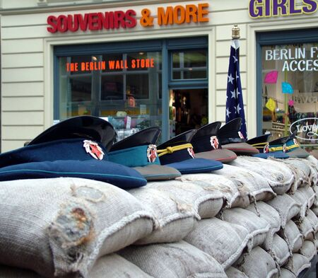 sectors: Checkpoint Charlie between east and west sectors during the Cold War with  the Soviet military caps on sandbags. Berlin,Germany
