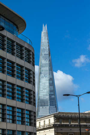 shard: The Shard towering over London on blue sky background, UK. Editorial