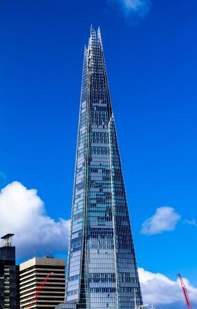 metres: The Shard towering over London on blue sky background,  tallest building in Europe at over 1,000 feet (310 metres).