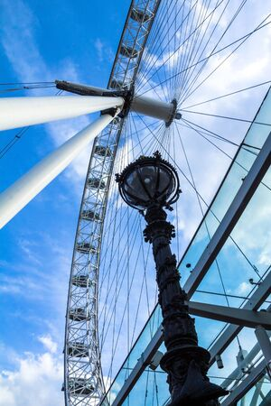 eye traveller: LONDON, UK - JUNE 6, 2015: Moving London Eye on blue sky background. London Eye is a giant Ferris wheel situated on the banks of the River Thames