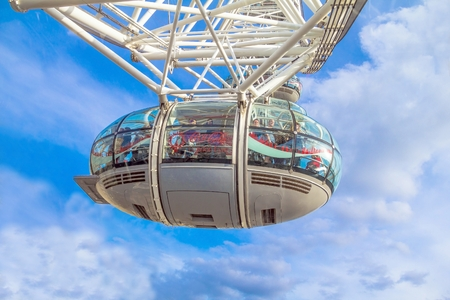 millennium wheel: LONDON, UK - JUNE 6, 2015: Unidentified people inside  London Eye  cabin on blue sky background. London Eye is a giant Ferris wheel situated on the banks of the River Thames Editorial
