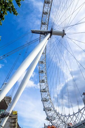 millennium wheel: LONDON, UK - JUNE 6, 2015: Moving London Eye on blue sky background. London Eye is a giant Ferris wheel situated on the banks of the River Thames, in London, England, United Kingdom Editorial