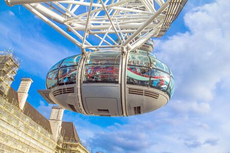 incidental people: LONDON, UK - JUNE 6, 2015: Unidentified people inside  London Eye  cabin on blue sky background. London Eye is a giant Ferris wheel situated on the banks of the River Thames Editorial
