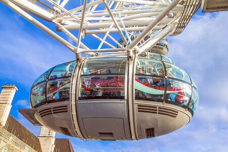 eye traveller: LONDON, UK - JUNE 6, 2015: Unidentified people inside  London Eye  cabin on blue sky background. London Eye is a giant Ferris wheel situated on the banks of the River Thames Editorial