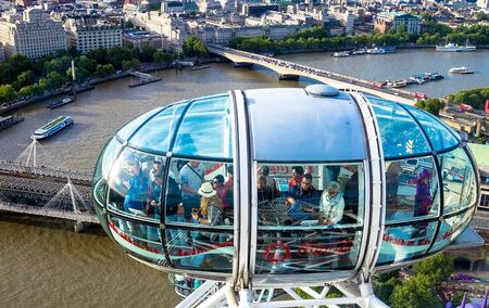 eye traveller: LONDON, UK - JUNE 6, 2015: Unidentified people inside  London Eye  cabin on cityscape background. London Eye is a giant Ferris wheel situated on the banks of the River Thames