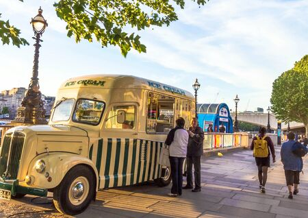 automobile dealer: LONDON, UK - JUNE 6, 2015:  Unidentified tourists are buying ice cream in an old automobile dealer at south bank of   the River Thames promenade at the  sunset time