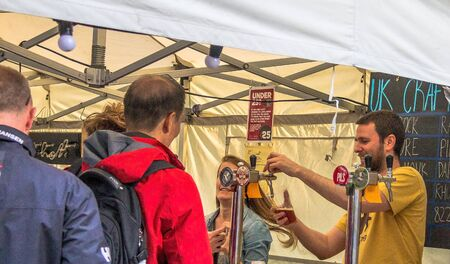 near beer: LONDON, UK - JUNE 6, 2015: Unidentified people standing in line  for draft craft beer  near  pub on the south bank of the River Thames