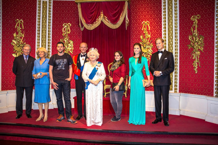 LONDON, UK - JUNE 7, 2015: Unidentified visitors are photographed for memory with The British royal family wax figures  At Madame Tussauds Wax Museum. Reklamní fotografie - 56237148