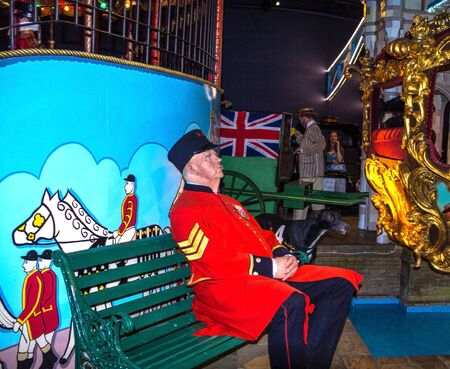 LONDON, UK - JUNE 7, 2015: Wax figure of Policeman in red uniform on the wooden bench at Canada Day in   Madame Tussauds museum