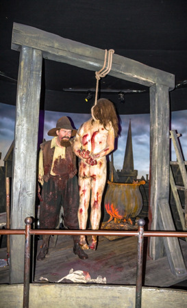 strangulation: LONDON , UK - JUNE 7, 2015:  Executioner  and gallows  at one of halls of historical part of  Madame Tussauds museum.  Madame Tussauds London is famous for recreating famous people and celebrities, in wax.