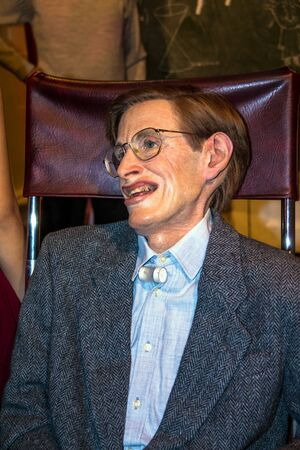 confined: LONDON - JUNE 7, 2015: The wax figure of the world famous American physicist and astrophysicist, an invalid, confined to a wheelchair, Stephen Hawking at Madame Tussauds museum. Editorial