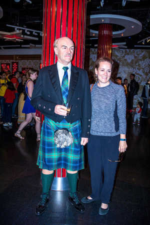 sean: LONDON , UK - JUNE 7, 2015: Unidentified girl makes photo for memory with Sean Connery wax figure in Madame Tussauds museum in London. Marie Tussaud was born as Marie Grosholtz in 1761