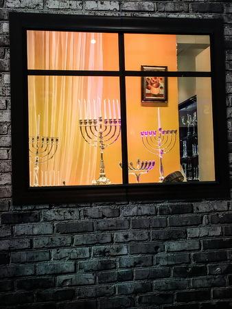 hanukka: TEL AVIV, ISRAEL - DECEMBER 22, 2016: Showcase of Judaic store before the Hanukkah holiday with exposed different sizes and designs menorahs (traditional candelabra)