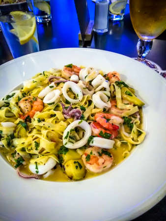 Healthy whole grain pasta with shrimps,calamari and herbs . Restaurant menu photo Stock fotó