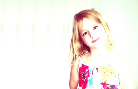 A cute six year old blonde girl in a summer white dress with flowers smiling on an abstract background with old photo effect as a film photo of the 70s