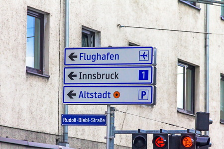 A traffic light with arrows and an exit sign for 1 highways in the direction of Innsbruck, Airport and Old Town. Salzburg. Austria