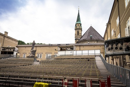 Traditional temporary concert hall in the open air for opera staging with Franciscan (Franziskaner ) Church and cloudy summer sky on background. Salzburg. Austria