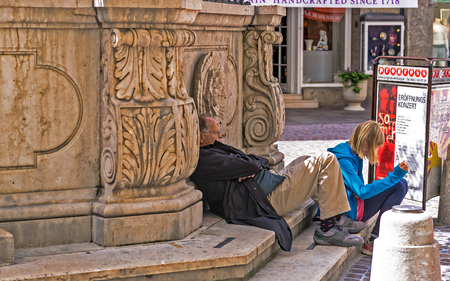 SALZBURG, AUSTRIA- July 15, 2017: Dad and daughter rest after a long excursion in the center of old Salzburg