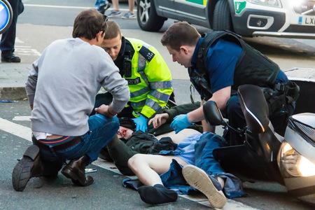 Londyn, Wielka Brytania - 7 czerwca 2015: Sanitariusze i strażacy udzielają pierwszej pomocy ofiarom wypadku motocyklowego na Piccadilly Street Publikacyjne