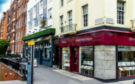 Historic buildings with different small businessis and stores. London. Blurred view