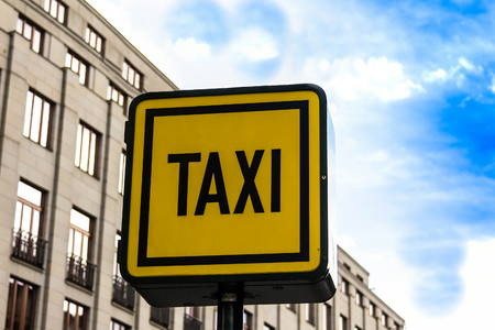 Information sign of a taxi on the background of houses in a European city.