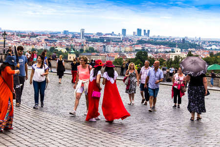 Prague, Czech Republic -July 23,2017: Japanese girls tourists in red clothes do selfie near Prague Castle, now official residence of the President of the Czech Republic