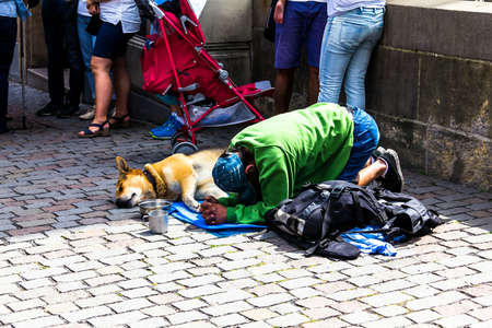 Prague, Czech Republic -July 23,2017: Homeless person begging in the historic streets of Prague Old Town centar full of tourists in characteristic pose, kneeling and not looking at the eyes of others.