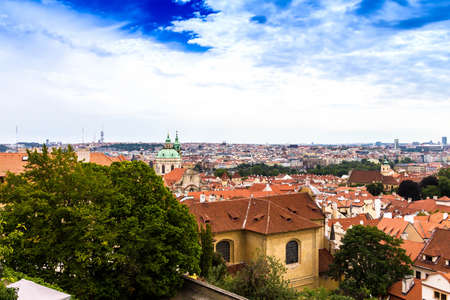 Summer aerial view of the Old Town architecture with red roofs and church of Saint Nicholas in Prague , Czech Republic.