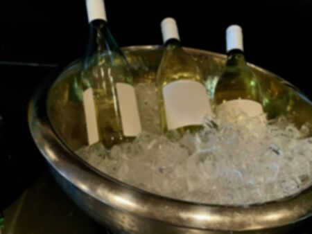 Close up on three bottles of white wine cooling in a bucket of ice. Blurred view