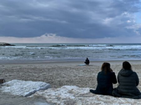 Two young women on the shore of a stormy sea. Surfer getting ready. Blurred view 版權商用圖片