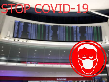 Stop COVID-19. Warning medical protection mask sign on airport flight schedule background.