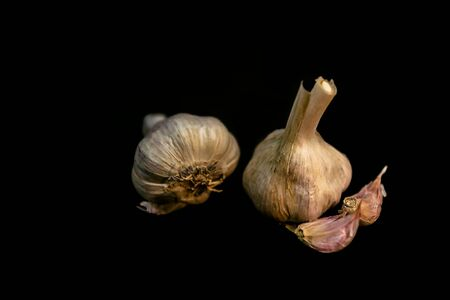 Fresh garlic on black background. Selective focus