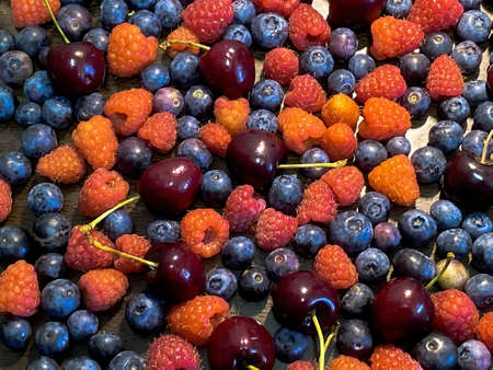 Blueberries, sweet cherry and raspberry scattered on a brown wooden table background 免版税图像