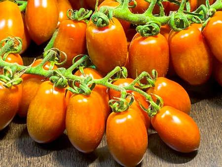Oblong cherry tomatoes on the vine over brown dark wooden table 免版税图像