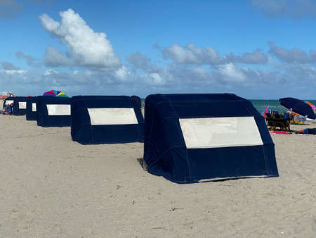 Blue hooded beach chairs or beach cabins at Baltic Sea or North sea sand Standard-Bild
