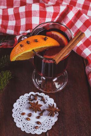 Glass of mulled wine on the table. Mulled wine with citrus slices on a table next to a Christmas tree branch and tablecloths. Stock Photo