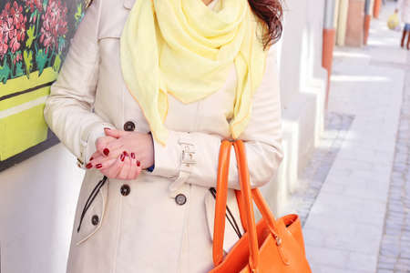 Stylish woman in beige coat with pale yellow scarf with bright orange leather handbad waking on the street. Street fashion look, vogue outfit