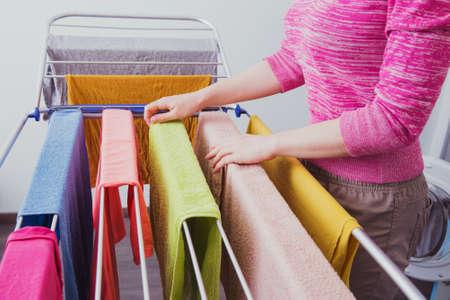Een jonge vrouw hangt kleren op de droger voor kleren na het wassen in een wasmachine. Inrichting voor het drogen van wasgoed na het wassen. Dames handen en natte kleding Stockfoto