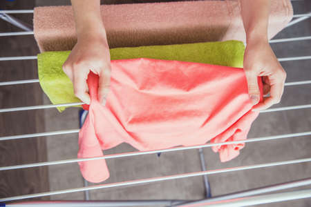 The housekeeper hangs up the laundry after washing. Home life. Female hands hang washed clothes on the dryer. Female hands with wet clothes. A woman hangs up wet clothes after washing.