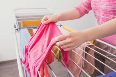 Female hands with wet clothes. A woman hangs up wet clothes after washing. Womens hands and wet clothes