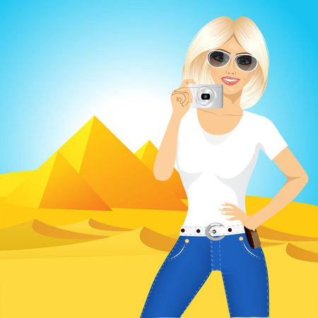 taking picture: portrait of young smiling pretty blonde woman in glasses taking a picture against Egyptian pyramids