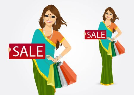 indian summer: portrait of cheerful traditional indian woman with shopping bags holding a red sign with sale text message