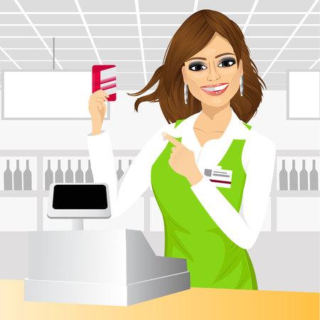 mujer en el supermercado: amable cajera señala en una tarjeta de crédito de pie en el mostrador de caja en el supermercado