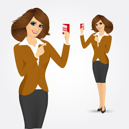 portrait of young female caucasian bank representative holding a credit card in one hand and pointing at it with the other isolated over white background