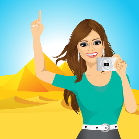 taking picture: portrait of young pretty woman woman taking a picture and pointing up against Egyptian pyramids
